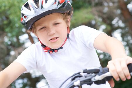 Low angle view of a smiling young boy in safety helmet riding bicycle at the park in summer. Stok Fotoğraf
