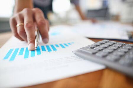 Afbeelding van mannenhand wijzend met pen op bedrijfsdocument tijdens bespreking tijdens vergadering close-up.