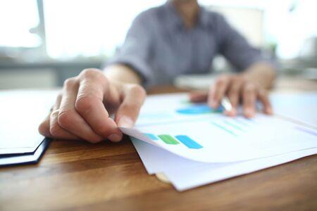 Close-up van een jonge zakenman die papier vasthoudt met financiële informatie, documenten bewerkt, marketingstrategie uitlegt of de economische groei van het bedrijf plant tijdens een brainstormvergadering op kantoor.