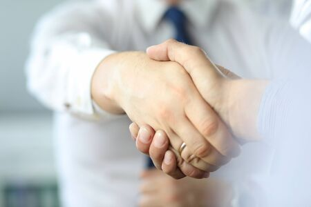 Closeup of business handshake after signing new contract at the office.