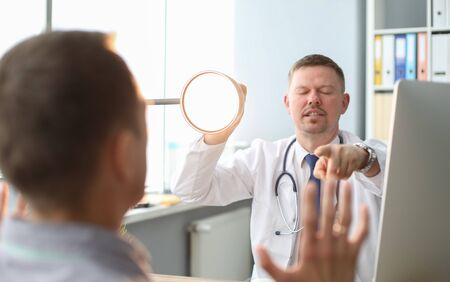 Angry doctor interrogates the patient, yelling at him, pointing to man he talking to and holding lamp base.
