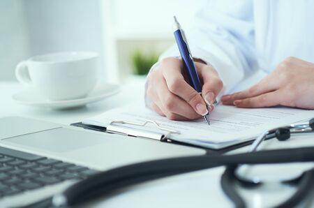 Sección intermedia de doctora escribe prescripción al paciente en la mesa de trabajo. Panacea y salva vidas, prescribiendo tratamiento.