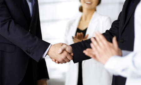 Unknown businesspeople are shaking their hands after signing a contract at meeting, close-up. Business communication concept