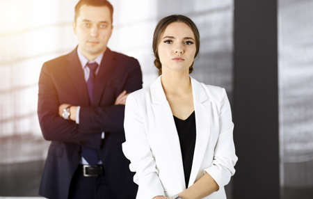 Young intelligent businesswoman is standing straight in a sunny modern office with her colleague at the background. Concept of successful business
