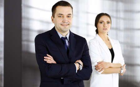 Portrait of a friendly middle aged businessman in a dark blue suit, standing with crossed arms together with a colleague in a modern office. Concept of success in a business