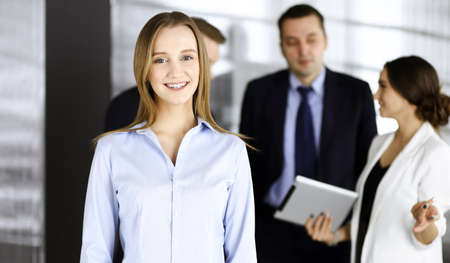 Young blonde businesswoman dressed in blouse is standing in a modern office. Concept of success in a business