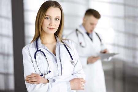Professional beautiful woman-doctor with a stethoscope is standing with crossed arms in a clinic. Young doctors at work in a hospital. Medicine and healthcare concept