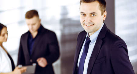 Portrait of a self-confident middle aged businessman in a blue suit, standing in a modern office with his colleagues at the background. Concept of business success