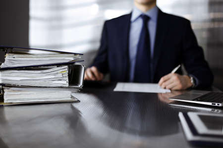 Binders with papers are waiting to be processed by man accountant in blue blazer staying at home during covid pandemic. Taxes and audit concept. Internal Revenue Service inspector checking financial document.