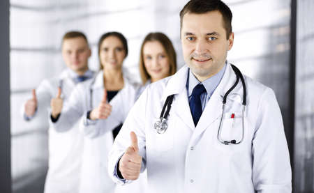 Group of professional doctors are standing as a team with thumbs up in a hospital office, ready to help their patients. Medical help, insurance in health care and medicine concept