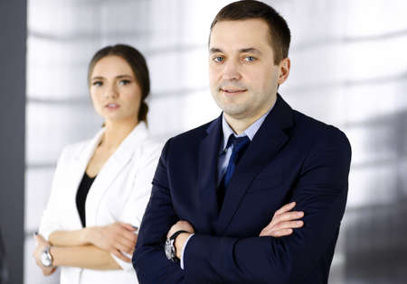 Portrait of a friendly middle aged businessman in a dark blue suit, standing with crossed arms together with a colleague in a modern office. Concept of success in a business Banco de Imagens