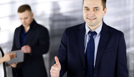 Portrait of a successful middle aged businessman, who is enjoying a good result of a teamwork, while standing at meeting in an office. Concept of success in a business Standard-Bild