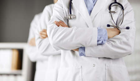 Group of modern doctors standing as a team with arms crossed in hospital office and ready to help patients. Medical help, insurance in health care, best disease treatment and medicine concept