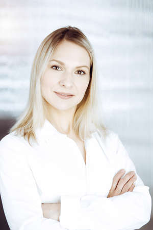 Friendly adult business woman standing straight. Business headshot or portrait in sunny office Standard-Bild