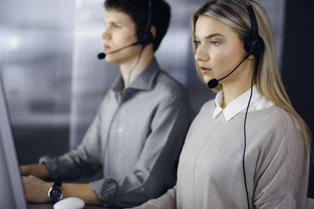 Diverse people group in call center. Blonde business woman talking by headset while sitting in modern office. Telemarketing and customer service concept