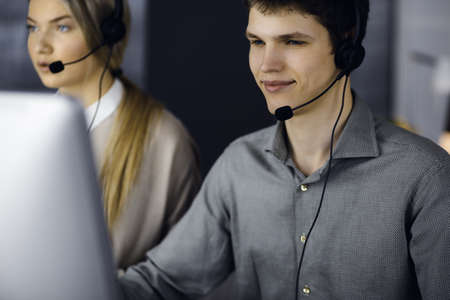 Diverse people group in call center. Businessman talking by headset while sitting in modern office