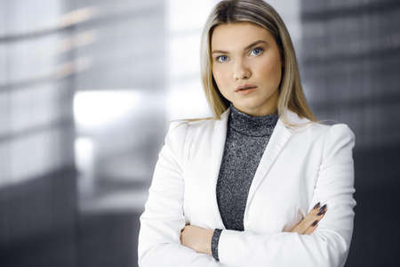 Young blonde business woman or female student in white blazer is standing straight and posing at camera. Lifestyle and diverse people concept