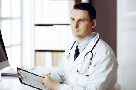 Friendly male doctor sitting and working with clipboard of medication history records in sunny clinic. Medicine and healthcare concept