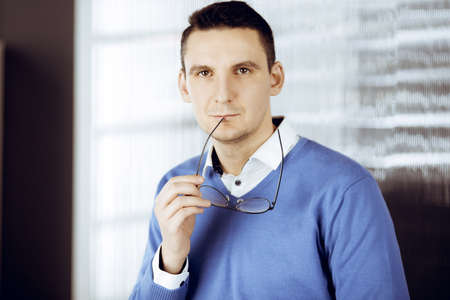 Friendly adult businessman in blue sweater. Business headshot or portrait in sunny office