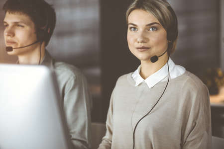 Diverse people group in sunny call center. Blonde business woman talking by headset while sitting in modern office Standard-Bild