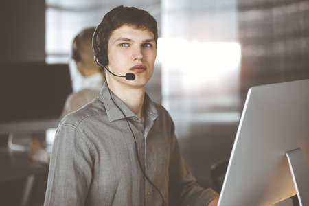 Businessman talking by headset while sitting in sunny office. Telemarketing concept Standard-Bild