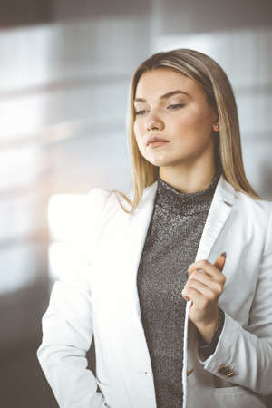 Young blonde business woman or female student standing straight and posing at camera in sunny office