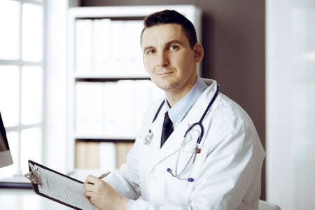 Friendly male doctor sitting and working with clipboard of medication history records in clinic at his working place. Perfect medical service in hospital. Medicine and healthcare concept
