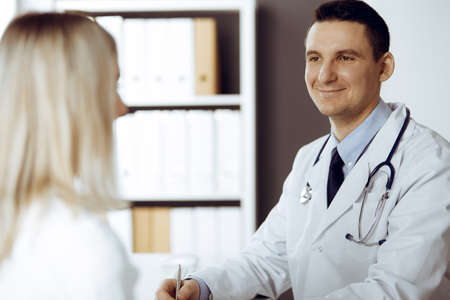 Friendly male doctor and patient woman discussing current health examination while sitting in sunny clinic. Perfect medical service in hospital Standard-Bild
