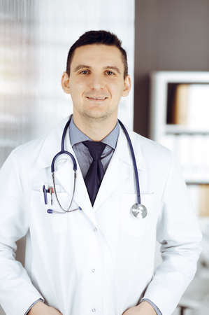 Male doctor standing straight in sunny clinic. Perfect medical service in hospital