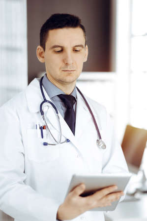 Friendly male doctor using tablet computer in sunny clinic. Medicine and healthcare concept Banque d'images