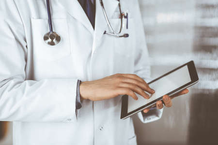 Unknown male doctor using tablet computer in clinic near his working place, closeup. Perfect medical service in hospital. Medicine and healthcare concept Banque d'images