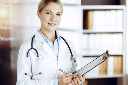 Friendly female doctor standing in sunny clinic. Portrait of cheerful smiling physician. Perfect medical service in hospital