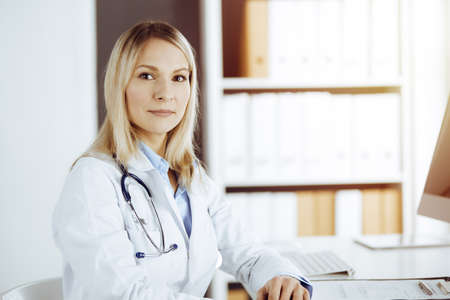 Friendly female doctor sitting in sunny clinic. Portrait of cheerful smiling physician. Medicine and healthcare concept Banque d'images