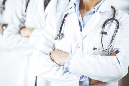 Group of modern doctors standing as a team with arms crossed in hospital office and ready to help patients. Medical help, insurance in health care, best disease treatment and medicine concept Banque d'images