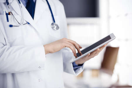 Unknown male doctor using tablet computer in sunny clinic, closeup. Perfect medical service in hospital. Medicine and healthcare concept Banque d'images