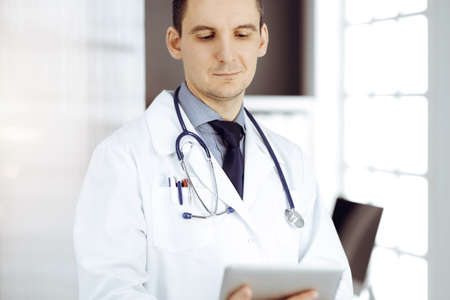 Friendly male doctor using tablet computer in sunny clinic. Medicine and healthcare concept Standard-Bild