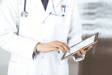 Unknown male doctor using tablet computer in clinic near his working place, closeup. Perfect medical service in hospital. Medicine and healthcare concept Standard-Bild