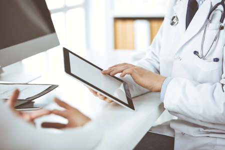 Unknown male doctor and patient woman discussing current health examination while sitting in clinic and using tablet computer. Perfect medical service in hospital. Medicine and healthcare concept Standard-Bild