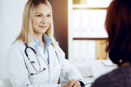 Friendly female doctor and patient woman discussing current health examination while sitting in sunny clinic. Perfect medical service in hospital