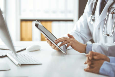 Unknown male doctor and patient woman discussing current health examination while sitting in clinic and using tablet computer, closeup of hands. Medicine and healthcare concept