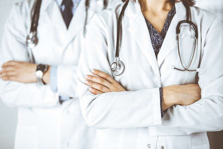 Group of modern doctors standing as a team with arms crossed in hospital office and ready to help patients. Medical help, insurance in health care, best disease treatment and medicine concept Standard-Bild
