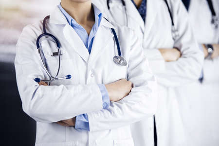 Group of modern doctors standing as a team with arms crossed in sunny hospital and ready to help patients. Medical help, insurance in health care