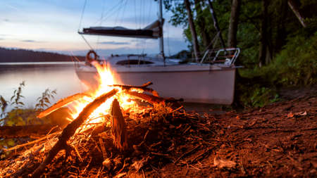 doldrums: Sailboat and campfire in Masuria Stock Photo