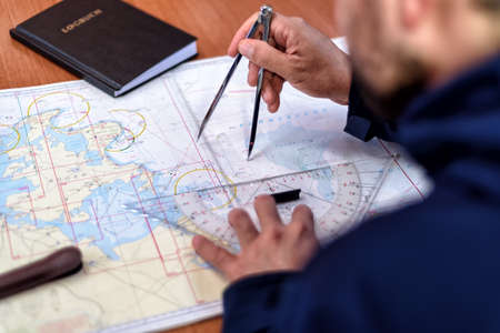 navigation with sea charts in the chart room on a sailing yacht