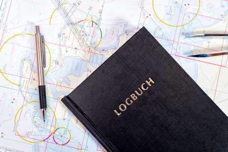 navigation book with sea charts in the chart room on a sailing yacht Foto de archivo