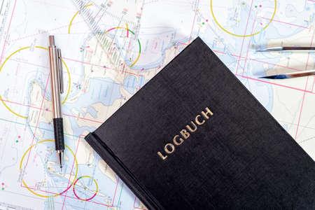 Navigationsbuch mit Seekarten im Kartenraum auf einer Segelyacht