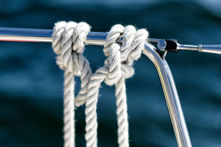 mooring lines hanging on the reeling on a sailing yacht on the ocean
