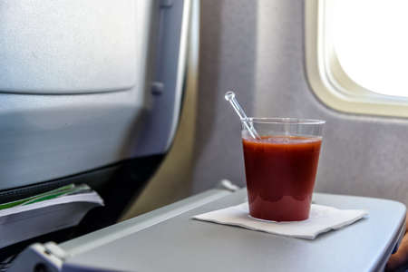 glas of tomato juice on a table in an airplane close to the airplane window