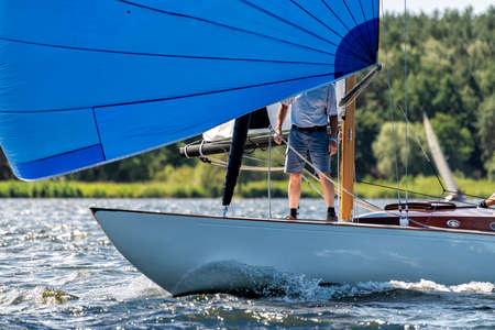 classic sailing yacht sailing with spinnaker on a lake during a regatta