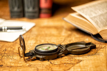 old expedition map with compass notebook, books and panama hat